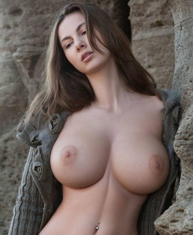 Прекрасная девушка у скалы с большими красивыми натуральными сиськами