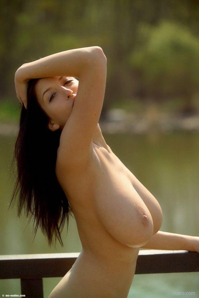 Брюнетка голая у воды с большими натуральными сиськами