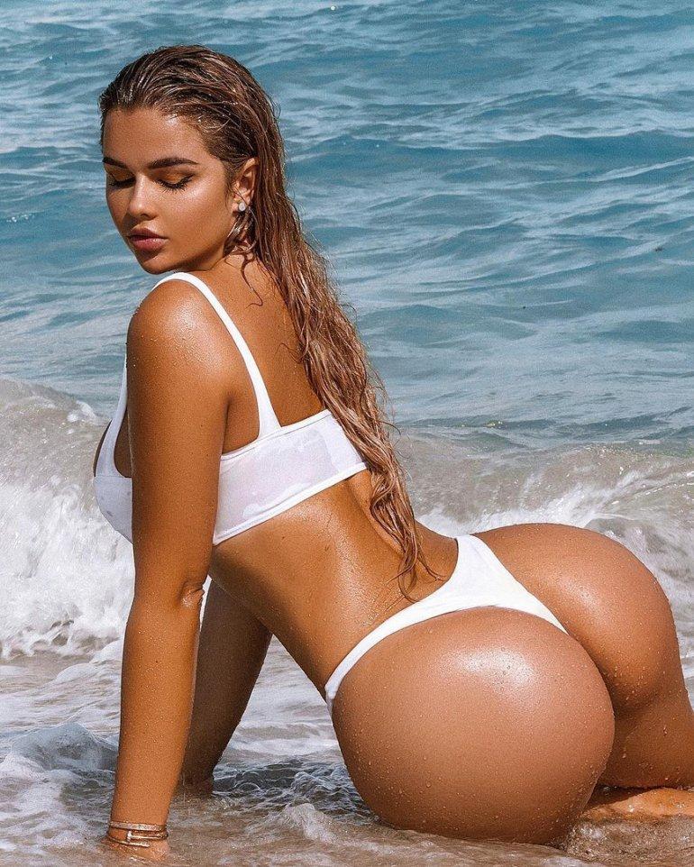 Загорелая девушка в белом купальнике с большой попой нежится в море