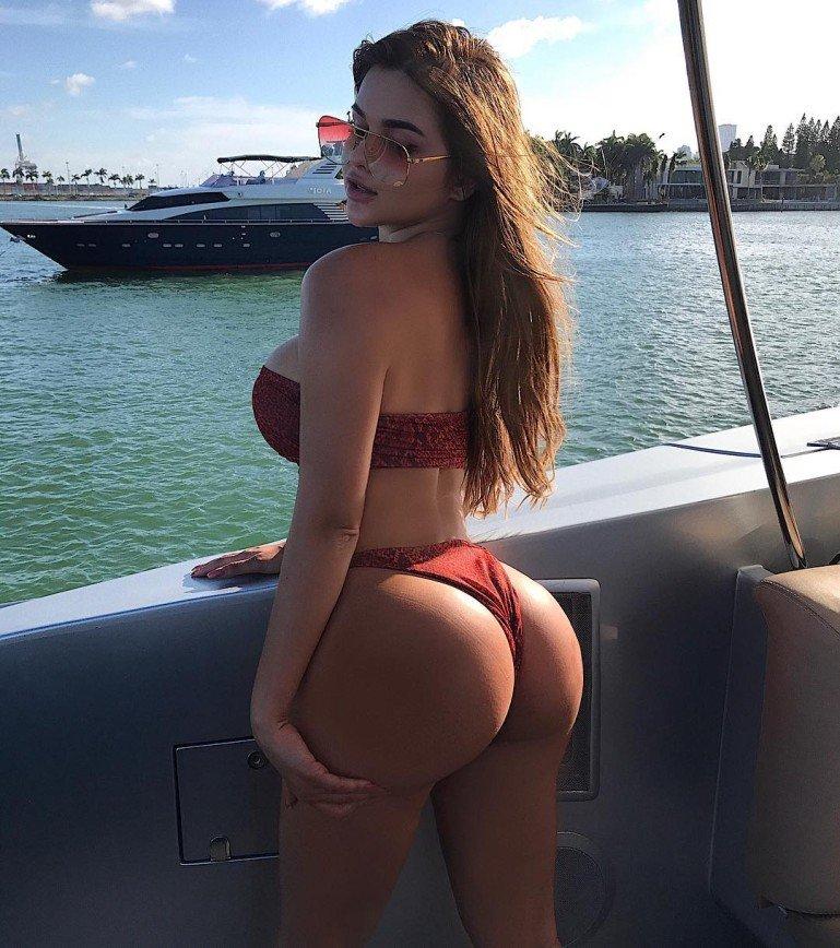 Молодая девушка на яхте гладит свою большую попу