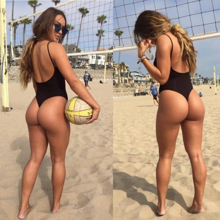 Девушка в не скромном купальнике с большой попой играет в волейбол