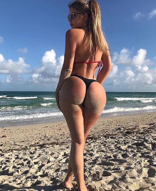 Девушка на пляже с красивой большой попой