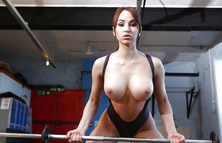 Сексуальная спортсменка с большими сиськами тянет штангу