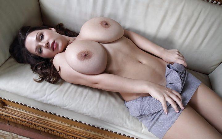 Возбужденная девушка лежит на диване с большими натуральными сиськами