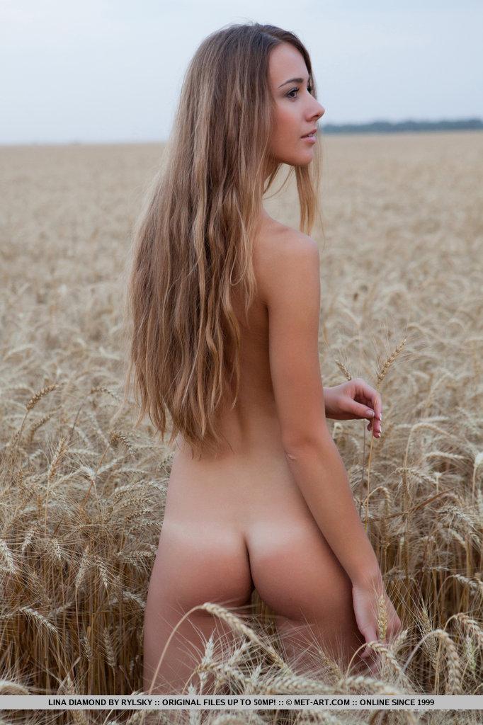 Романтическая девушка с маленькой попой голая гуляет в поле