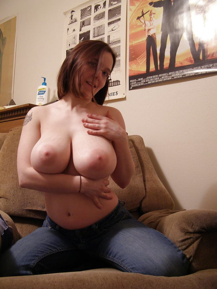 Милая женщина на диване сняла майку и обнажила свои упругие большие натуральные сиськи
