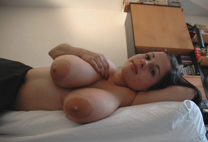 Милая девушка лежит в кровати с обнаженной большой натуральной грудью