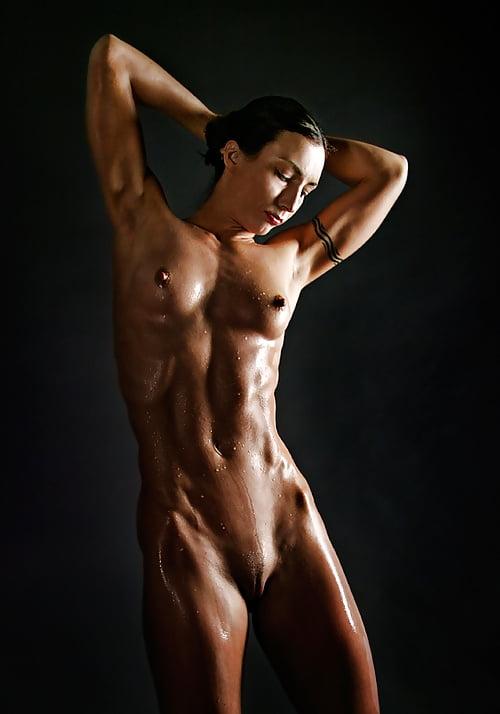 Мокрая стройная голая девушка с миниатюрной грудью и татушкой на руке