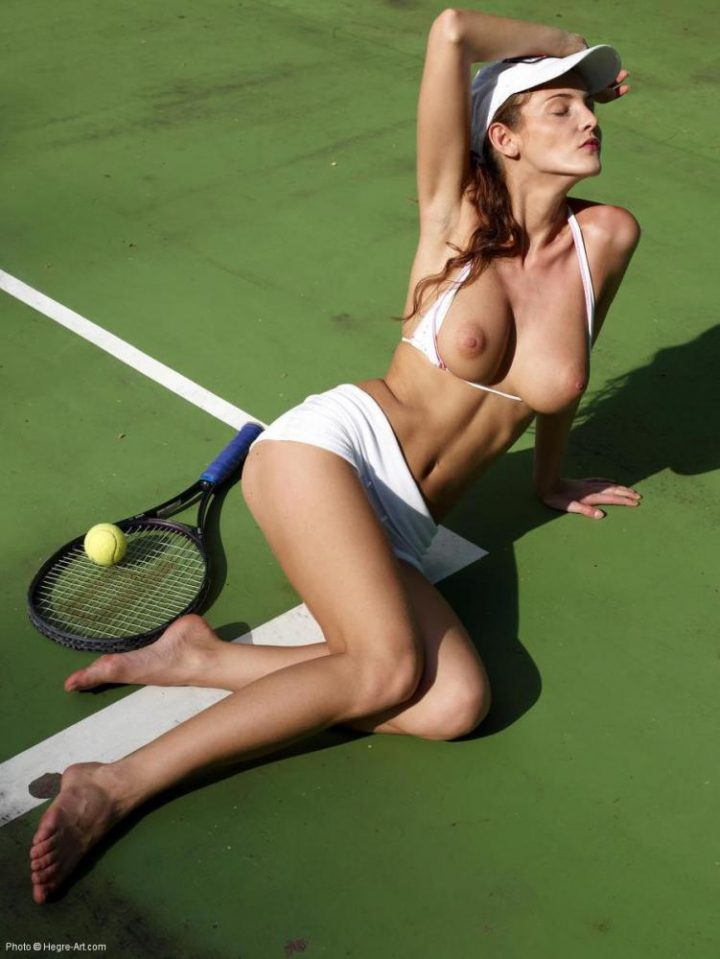 Красивая спортсменка теннисистка лежит на корте с обнаженной грудью