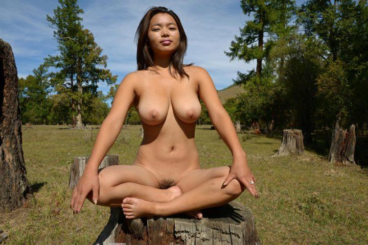 Прекрасная северная девушка голая медитирует на пне