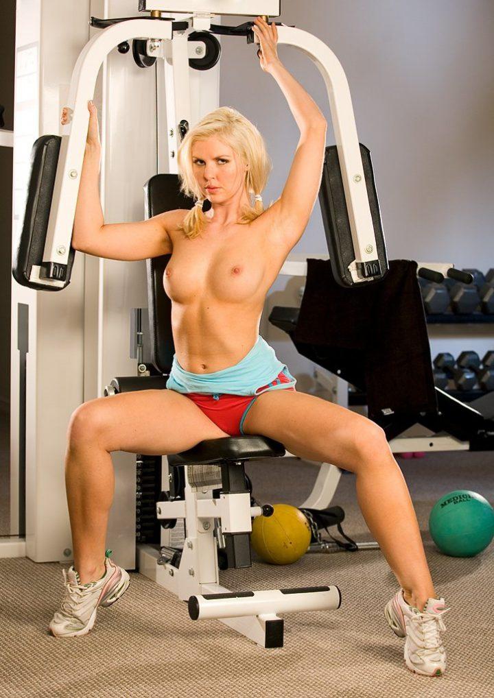 Красотка блондинка с голой грудью в одних трусиках занимается фитнесом