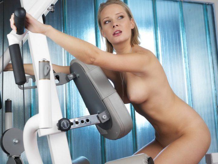 Милая девушка без одежды занимается на тренажере
