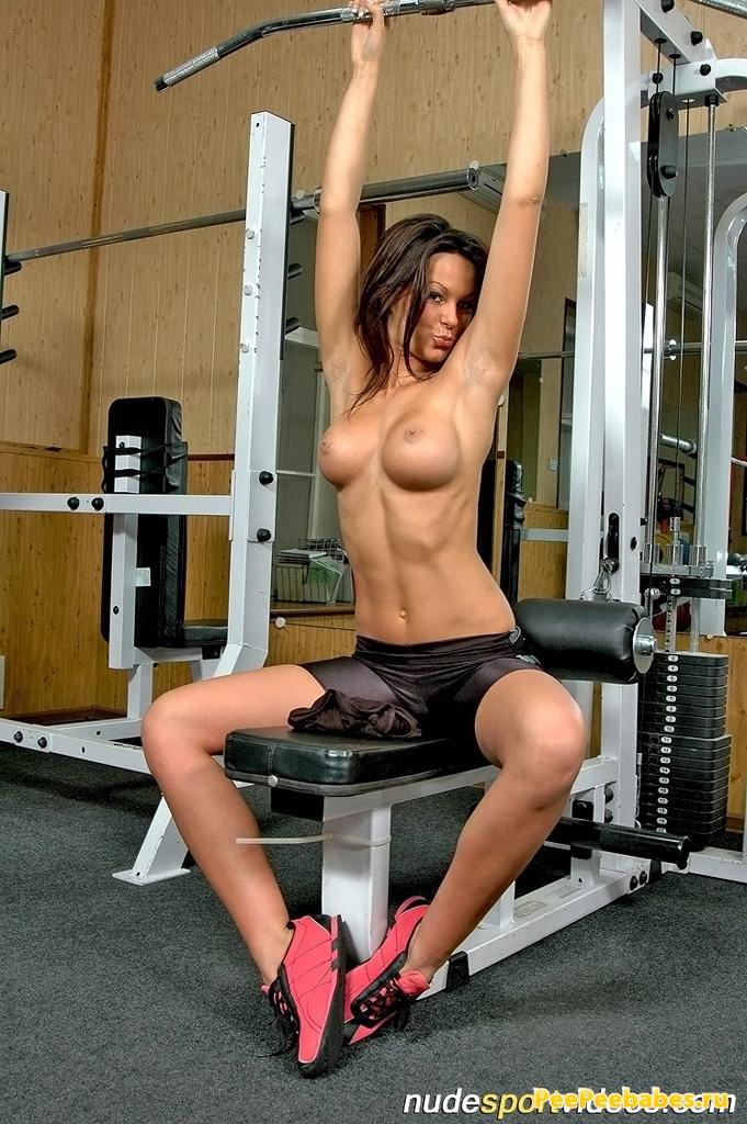 Спортивная девушка с голыми упругими сиськами занимается на тренажере