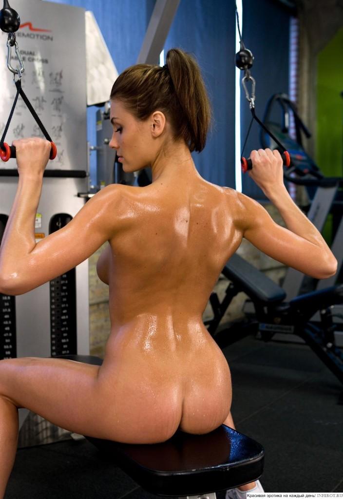 Девушка абсолютно голая в спортзале качает спину