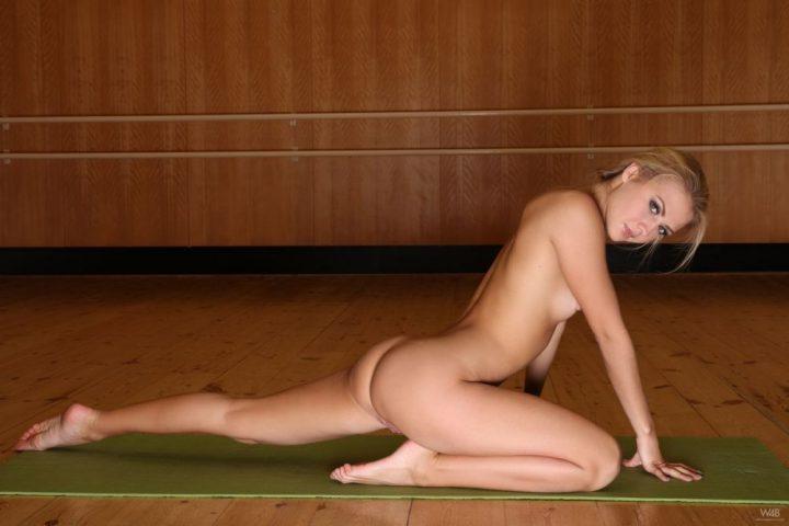 На тренировке девушка без одежды выполняет растяжку