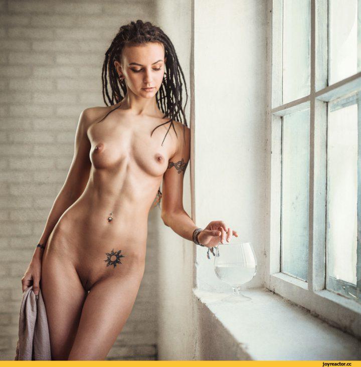 Интересная девушка с дредами и тату на теле стоит полностью голая с упругой маленькой грудью