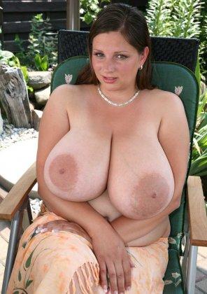 На фото женщина сидит в шезлонге с огромным натуральными сиськами