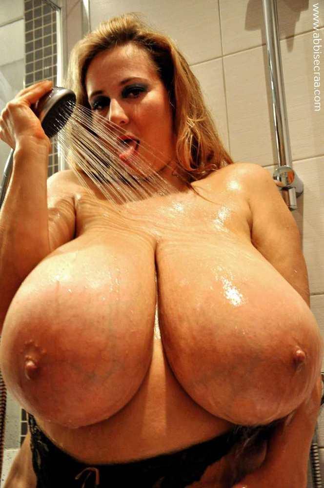 Девушка с огромными сиськами играет с душем