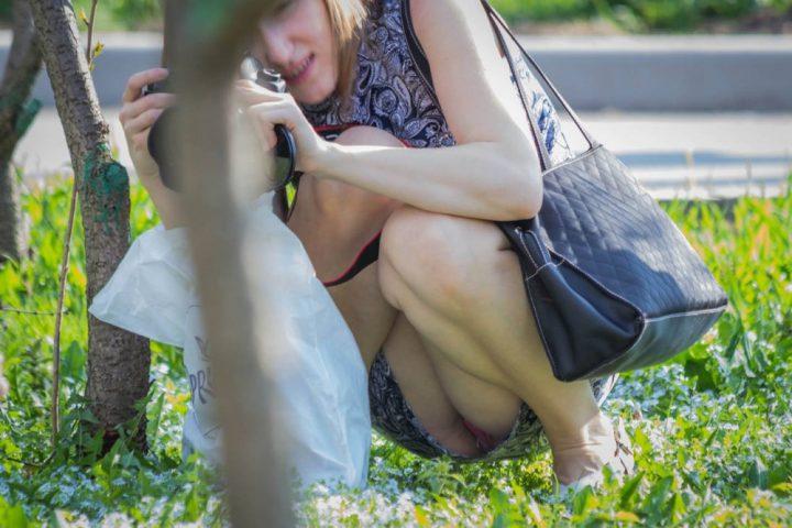 Девушка на корточках что то фотографирует, а в это время фоткают ее письку в платье без трусов