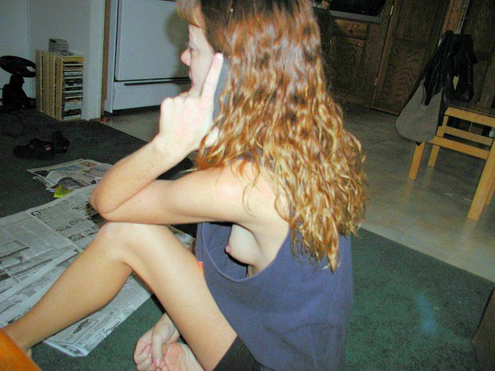 Девушка разговаривает по телефону в огромной майке светя своими маленькими сиськами