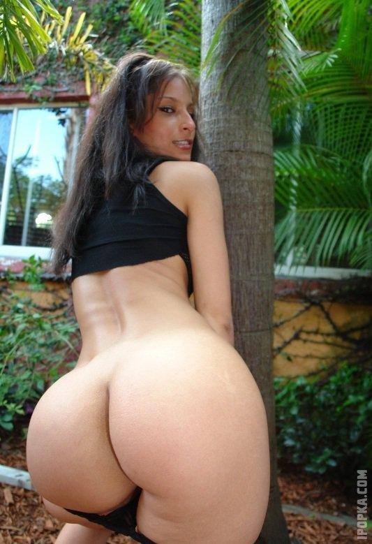 Брюнетка возле пальмы в одной короткой майке и с голой огромной попой
