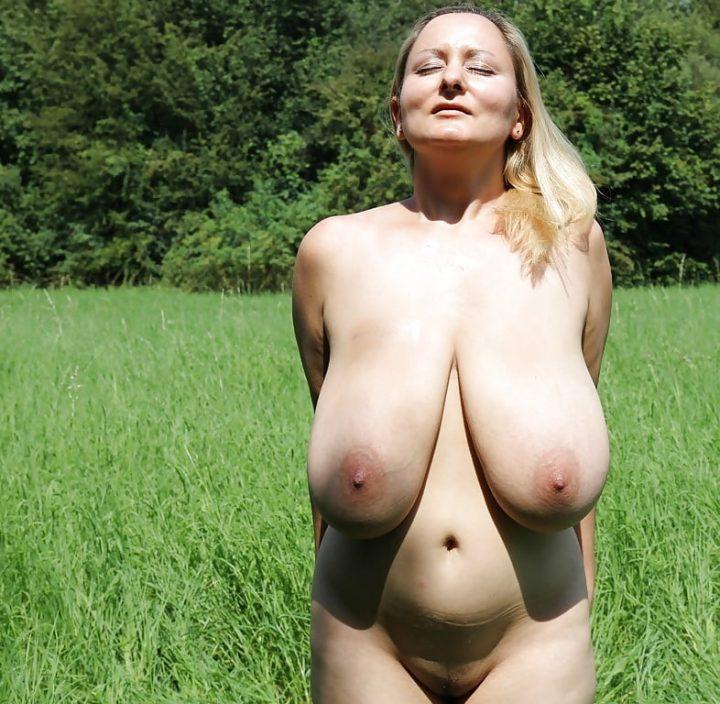 Русская баба в поле с голыми огромными сиськами греется на солнце