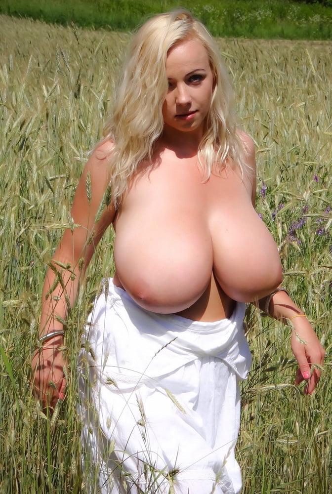 Русская баба с огромными натуральными сиськами гуляет по полю