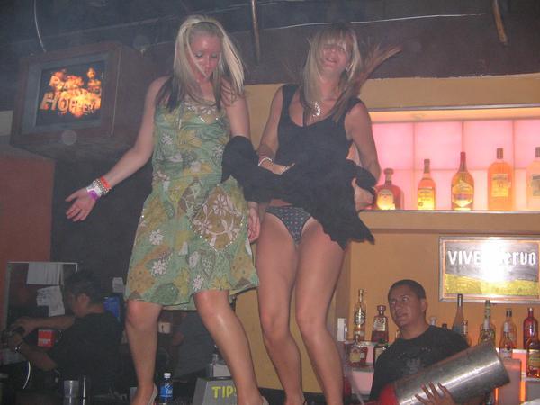 Пьяная девушка залезла на стойку и танцует зажигательный танец задрав юбку
