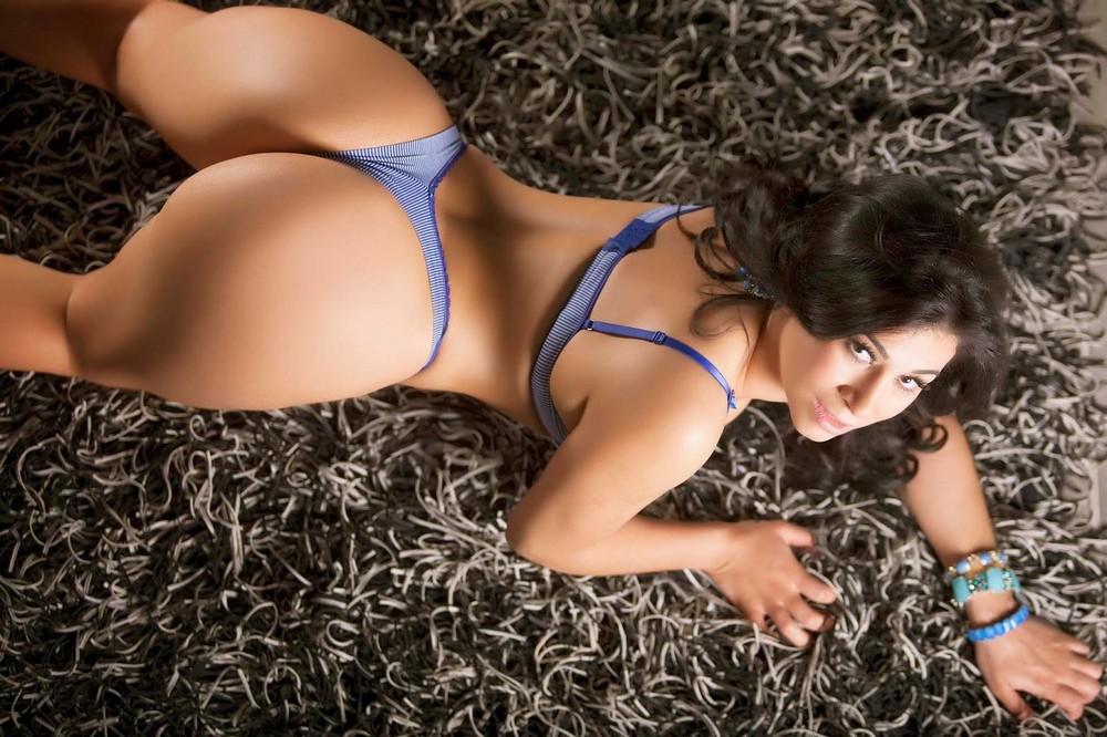 Девушка лежит на животе на пушистом ковре, показывая бразильскую попу