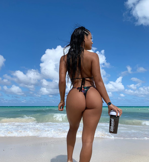 Девушка стоит спиной с бутылкой воды в красивом бикини показывая идеальную бразильскую попу