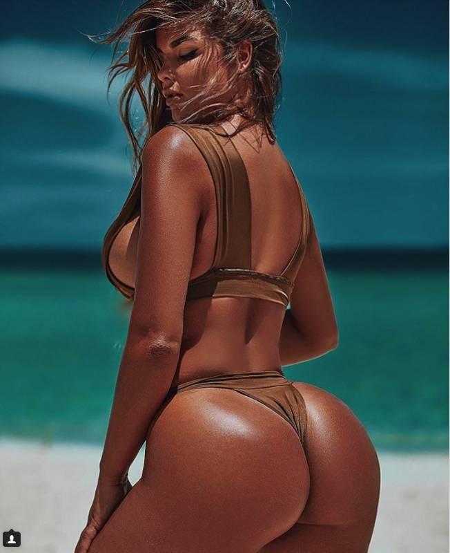 Девушка с очень сильным загаром в бикини с большой бразильской попой
