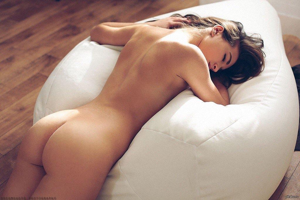 Уставшая голая девушка с красивой попой лежит на кресле