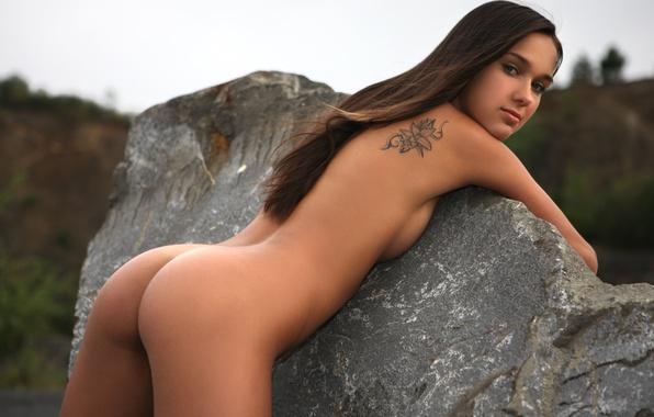 Молодая стройная девушка с красивой попой обняла камень
