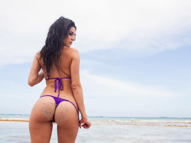 Девушка на морском берегу с красивой попой снимает купальник