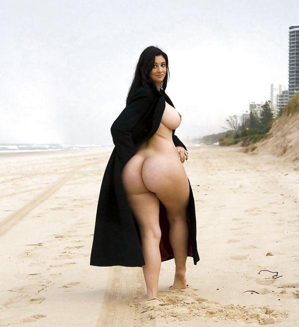 Обнаженная девушка с широкими бедрами и большими сиськами в плаще гуляет по пляжу