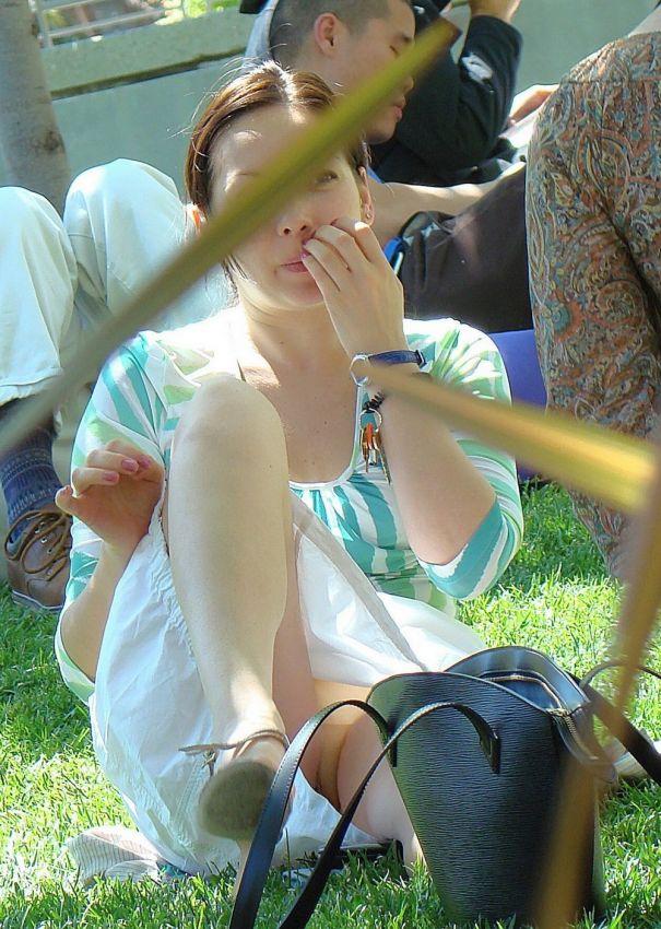 Женщина в парке сидит на траве, и не замечает что видно ее голую письку
