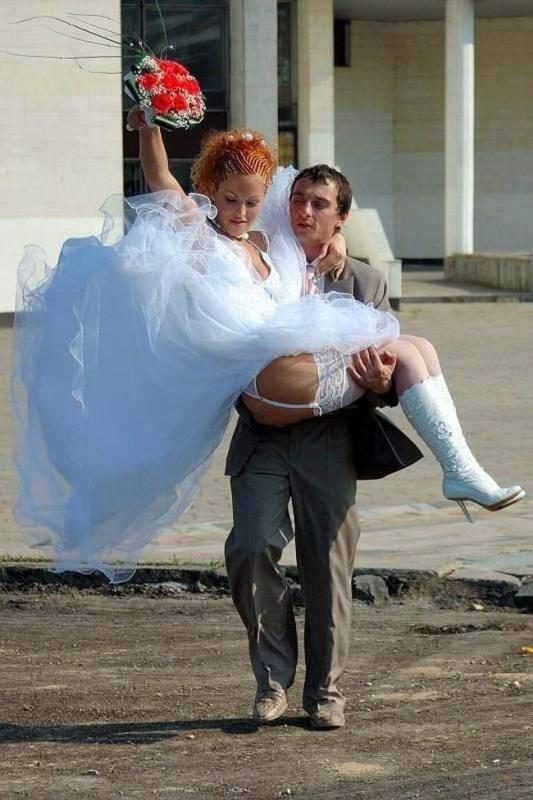 Жених несет невесту на руках, что видно ее бедра и чулки на поясе