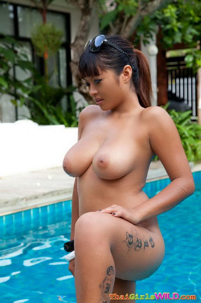 Молодая тайка с татуировкой на бедре и голыми сиськами