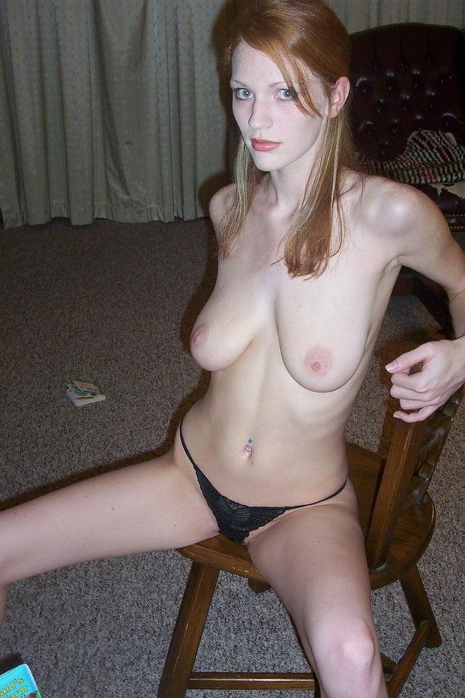 Не скромная рыжая девушка сидит на стуле в трусиках с голыми висячими сиськами