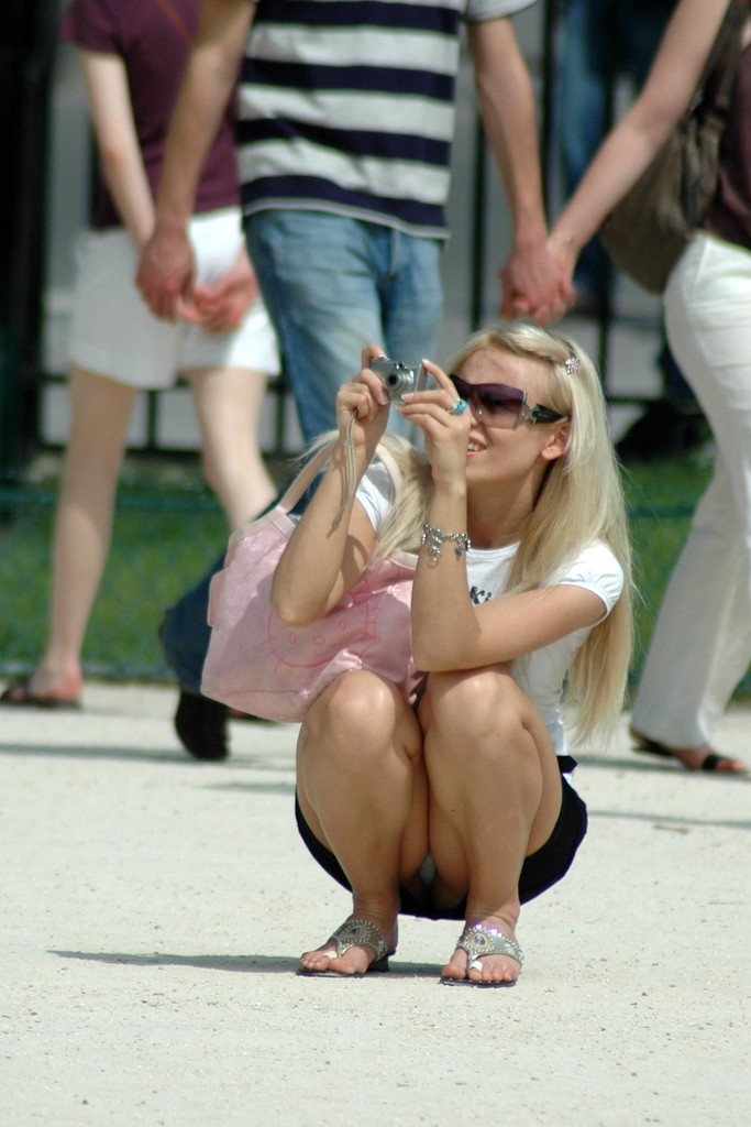 Девушка с увлечением фотографирует сидя на корточках и светит трусиками