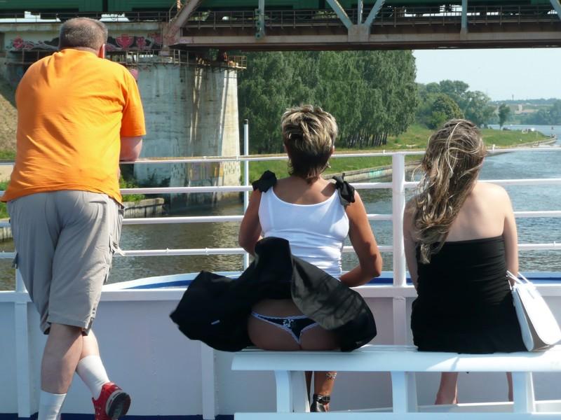 Женщина с короткой стрижкой в стрингах катается на катере