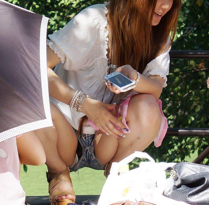 Девчонка сидит на корточках и светит трусами в мини шортах