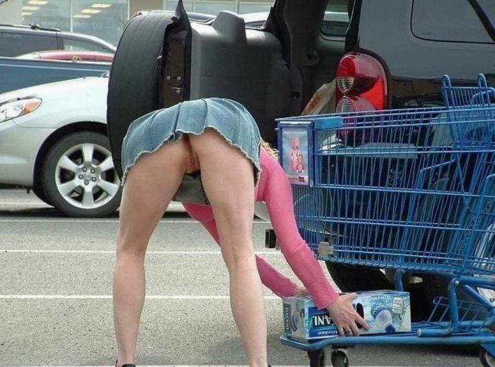 Женщина складывает покупки в короткой юбке, а трусы надеть забыла