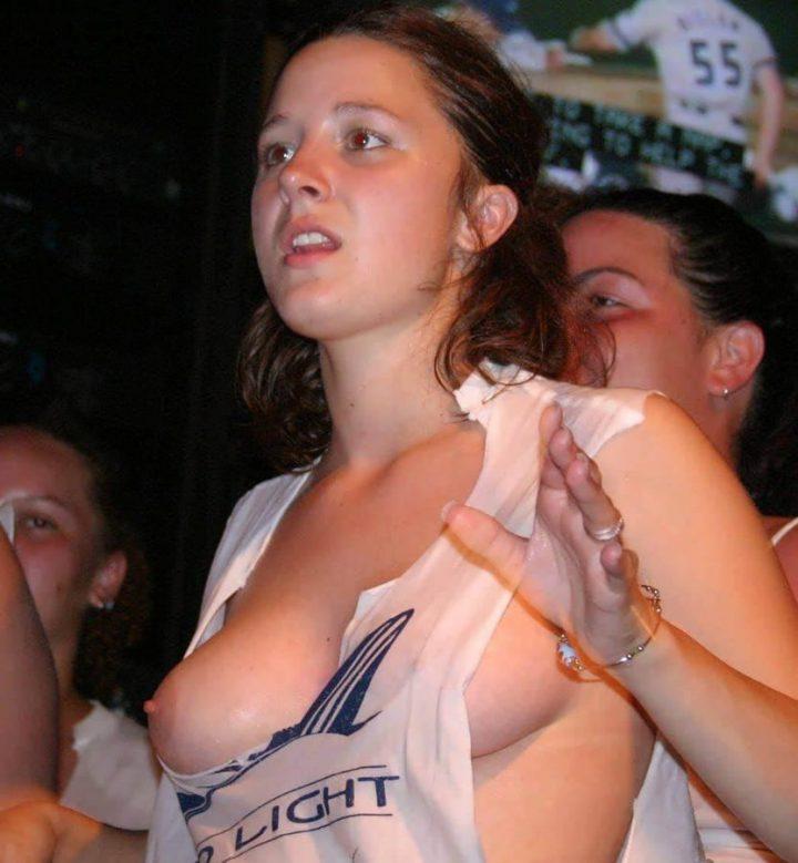 У молодой девушки намок топ и оголил упругую грудь