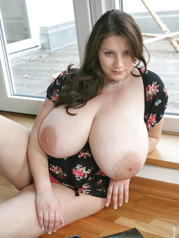Женщина сидит у окна, и демонстрирует большие натуральные сиськи