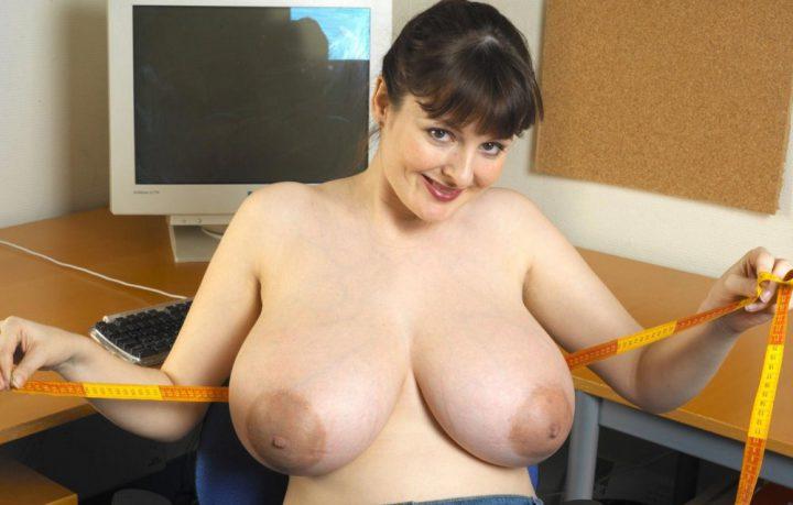 Женщина на рабочем месте измеряет свои большие зрелые сиськи