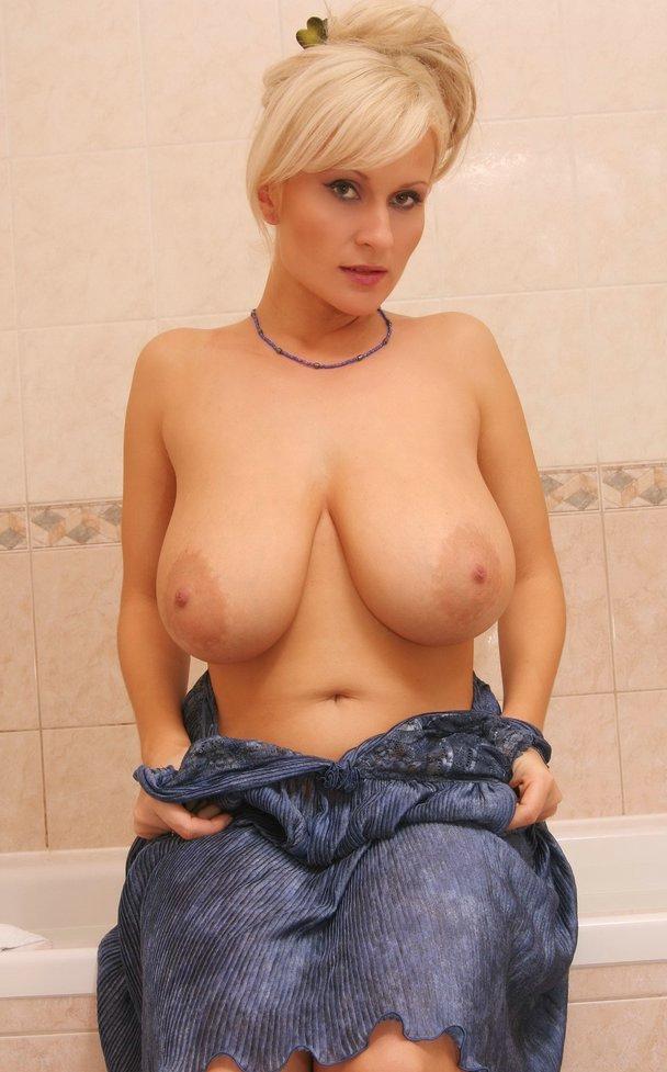 Женщина сидит полуобнаженная в ванне с большими зрелыми сиськами