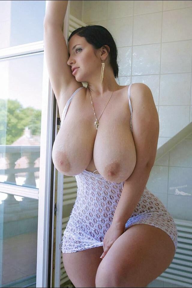 Женщина у окна стоит с голыми зрелыми сиськами