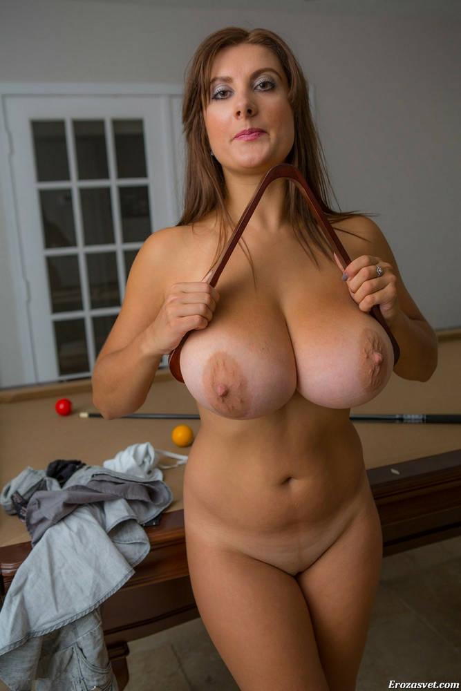 Ярко накрашенная голая женщина зажала свои большие зрелые сиськи