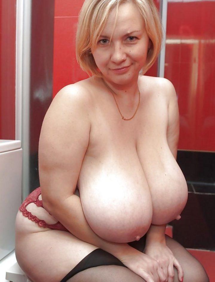Пышная женщина в ванной сидит и позирует большими голыми зрелыми сиськами